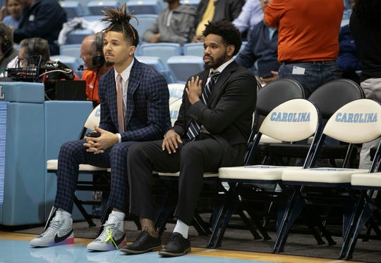 North Carolina's Cole Anthony, left,and Jeremiah Francis, both out with injuries, watch their teammates warm up for an NCAA college basketball game against Clemson on Jan. 11, 2020, at the Smith Center in Chapel Hill.