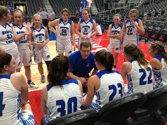 Harper Creek girls basketball team listen to head coach Phil Hicks during a timeout in a game against Hastings at Little Caesars Arena.