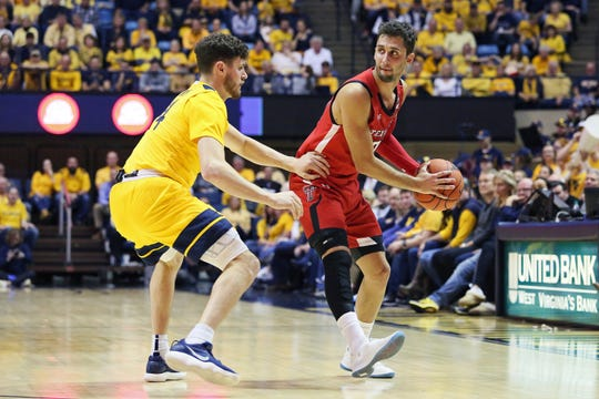 Texas Tech guard Davide Moretti, right, looks to pass the ball as he is defended by West Virginia guard Chase Harler, left, during the first half of an NCAA college basketball game Saturday, Jan. 11, 2020, in Morgantown, W.Va. (AP Photo/Kathleen Batten)