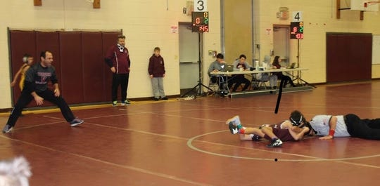 Chase Falcone, 8, records his first career pin, while his father, Jamie (left), a former wrestler at the University of Maryland, watches