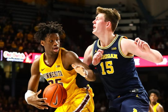 Minnesota center Daniel Oturu in action against Michigan center Jon Teske in the first half on Sunday, Jan. 12, 2020, in Minneapolis.