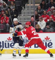 Detroit Red Wings defenseman Mike Green checks Buffalo Sabres center Zemgus Girgensons during the second period at Little Caesars Arena in Detroit, Sunday, Jan.12, 2020.