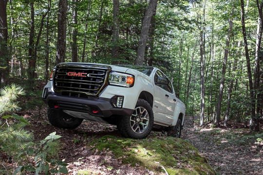 The 2021 GMC Canyon AT4 midsize pickup has a black chrome grille and skid plate to protect its transfer case.