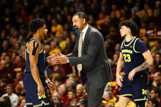 Michigan coach Juwan Howard gives instruction to guard David DeJulius in the first half on Sunday, Jan. 12, 2020, in Minneapolis.