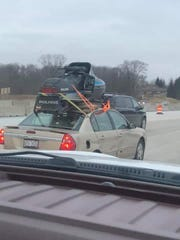 A photo a fellow driver snapped of Tommy Mecher making his way through the Midwest with his new snowmobile strapped to the roof of his car.