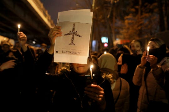 People gather for a candlelight vigil to remember the victims of the Ukraine plane crash, at the gate of Amri Kabir University that some of the victims of the crash were former students of, in Tehran, Iran, Saturday, Jan. 11, 2020.