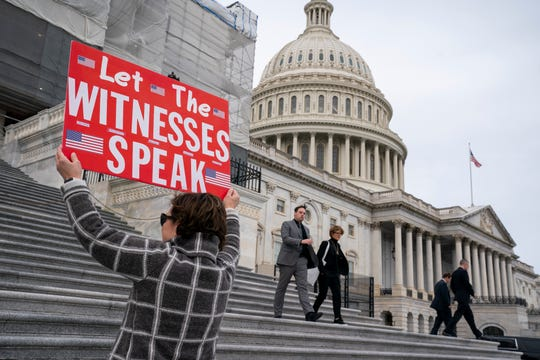 Laura Albinson of Pasadena, Md., displays a message for members of the House as they leave the Capitol in Washington, Friday, Jan. 10, 2020.