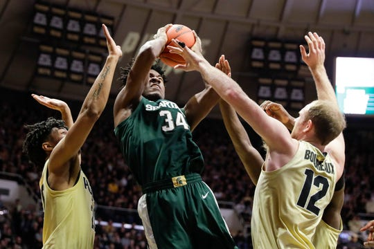 Michigan State forward Julius Marble is defended by Purdue forward Evan Boudreaux (12) and Purdue guard Nojel Eastern (20).