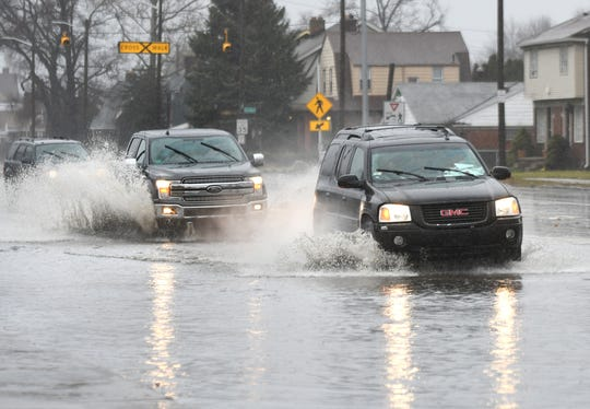 Motorist travel through a flooded intersection at Dexter Avenue at Davidson Highway in Detroit on Saturday, Jan. 11, 2020.