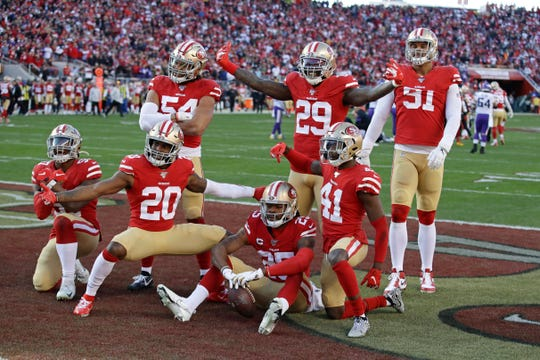 San Francisco 49ers players celebrate after cornerback Richard Sherman (25) intercepted a pass against the Minnesota Vikings during the second half of a divisional playoff game.