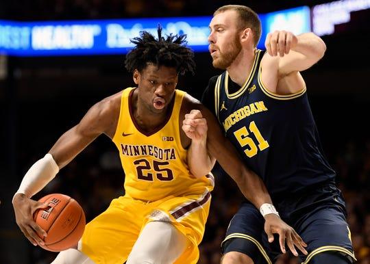 Michigan's Austin Davis guards against Minnesota's Daniel Oturu.