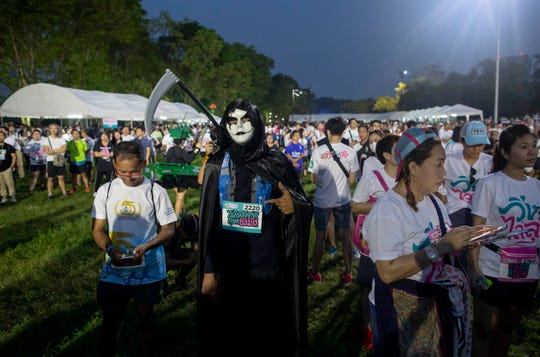 """A supporter of the anti-military Future Forward Party in a costume gather for a run dubbed as """"Run Against Dictatorship"""" at a park in Bangkok, Thailand, Sunday, Jan. 12, 2020"""