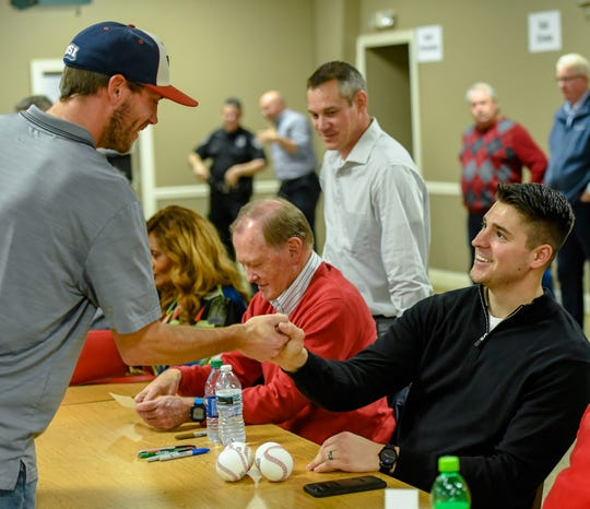 Jerad Eickhoff (sitting) shakes hands with Andy Lasher of Newburgh at the recent Night of Memories at the Vanderburgh 4-H Center.