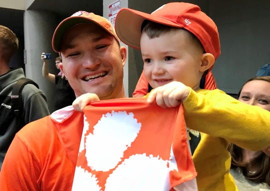 Two-year-old Clemson fan Hunter Walerko waits to greet the Clemson football team in New Orleans along with his father, P.J., and mother, Melissa.