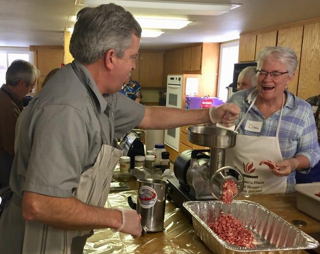 Rep. Frank Garner, R-Kalispell, puts meat into the grinder Sunday as he prepares sausage with Sen. Diane Sands, D-Missoula.