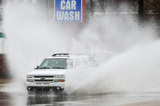 A vehicle plows through high water traveling south on Keystone Avenue at Binford Boulevard amidst a flood warning in Indianapolis, Saturday, Nov. 18, 2017.