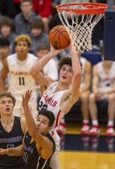 Plainfield High School sophomore Cael Vanderbush (22)puts up a shot over Brownsburg High School junior Pierce Thomas (11) during the second half of action in the championship game of the 2020 Hendricks County Boys' Basketball Tournament, Saturday, Jan. 11, 2020, at Tri-West High School. Brownsburg won 55-43.