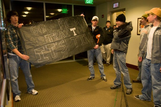 Upset fans hold a sign that displays their attitude as they wait for Lane Kiffin to announce his resignation on Tuesday, Jan. 12, 2010.