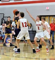 Bloom-Carroll's Trace Wisecarver looks for a team against Fairfield Union's Sam Bernard and Chase Poston during Friday's Mid-State League-Buckeye Division game. The Falcons won, 40-38.