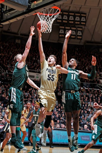 Jan 12, 2020; West Lafayette, Indiana, USA; Purdue Boilermakers guard Sasha Stefanovic (55) takes a shot against Michigan State Spartans forward Thomas Kithier (15) and forward Aaron Henry (15) during the second half at Mackey Arena. Mandatory Credit: Brian Spurlock-USA TODAY Sports