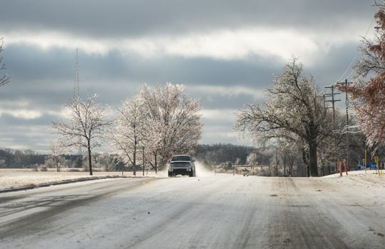 A truck drives down Collins Road Sunday morning, Jan. 12, 2020, amongst ice laden trees.
