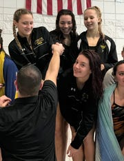 Lexington coach Brock Spurling hands out first place medals to his 200 medley relay team of (top, left to right) Tessa Gerhardt, Olivia Newman and Sarah Malaska and (bottom) Lily Weeks at the Ohio Cardinal Conference swim meet