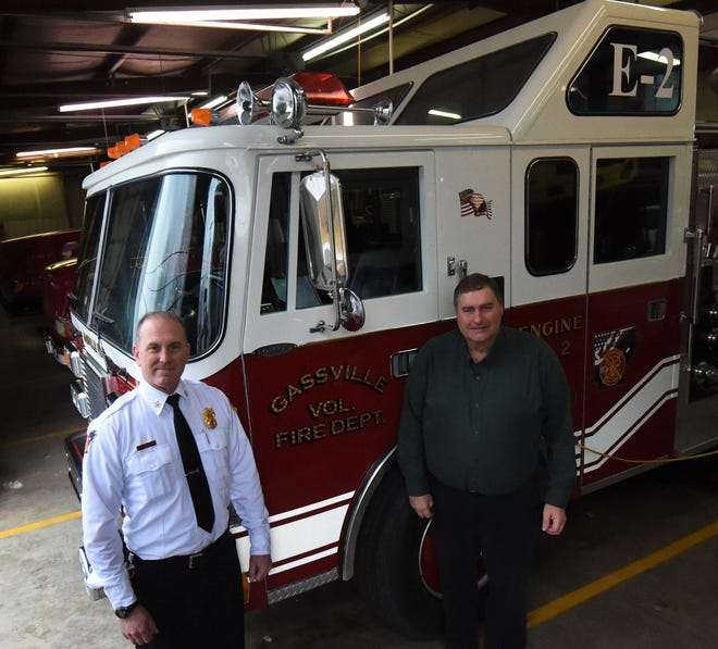 Gassville Fire Chief Michael Glotzl (left) and Mayor Jeff Braim (right) stand in front of one of the city's engine trucks on Friday afternoon. The city has been awarded a Class 2 Public Protection Classification, which should lower residents' fire insurance premiums when the rating goes into effect in April.