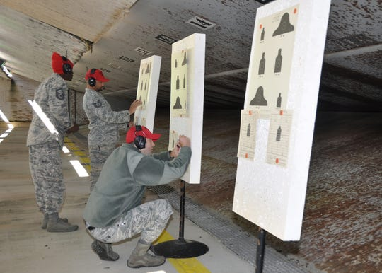 From left, Master Sgt. Henry Relf, Tech. Sgt. Shannon Jones and Staff Sgt. Jonathan Pilgrim, 908th Security Forces Squadron Combat Arms instructors, review targets Nov. 2, 2019, in the firing bay at Maxwell AFB, Alabama. Every year, the SFS defenders have to score high enough to re-qualify with both the M4 carbine and the M9.