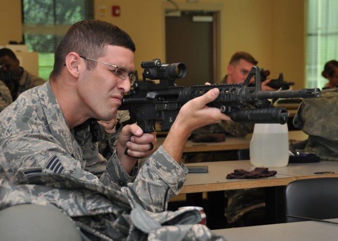 Staff Sgt. Jacob Williams, 908th Security Forces Squadron defender, aims his M4 carbine Nov. 2, 2019, in a classroom at Maxwell AFB, Alabama. Airmen are required to have hours of classroom instruction by Combat Arms instructors before they can use their weapons at the firing range.