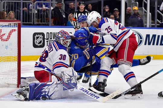 Jan 11, 2020; St. Louis, Missouri, USA;  New York Rangers goaltender Henrik Lundqvist (30) makes a save as New York Rangers defenseman Libor Hajek (25) checks St. Louis Blues center Oskar Sundqvist (70) during the second period at Enterprise Center. Mandatory Credit: Jeff Curry-USA TODAY Sports