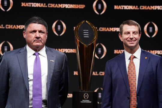 LSU coach Ed Orgeron, left, and Clemson coach Dabo Swinney with the national championship trophy