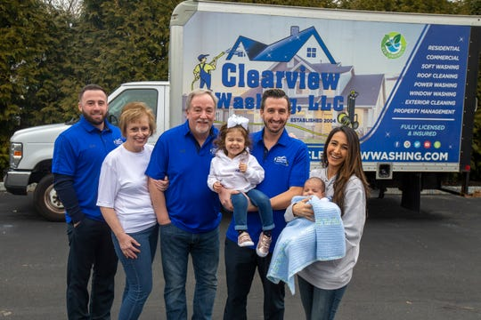 (L-R) Steven Hodge, Maria Hodge, Fred Hodge, Sr, Gabrielle Hodge, 2, Fred Hodge, Jr, Christine Hodge and William Hodge, 2 months, pose in front of the truck of their family business, Clearview Washing, a nearly 16-year-old Freehold-based company that specializes in residential and commercial window washing, pressure washing, soft washing and roof washing, in Freehold, NJ Monday, January 13, 2020.