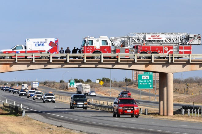 Taylor County EMS and Abilene Fire Department personnel are stationed at Fulwiler Road overpass at Interstate 20 on Monday, as the bodies of fallen Lubbock firefighter Eric Hill and police officer Nicholas Reyna are escorted from Fort Worth following an autopsy.