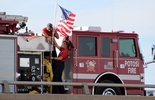 David Hamilton and Taryn Riden of the Potosi Volunteer Fire Department prepare the U.S. flag for display over the Buck Creek Road overpass of Interstate 20 east of Abilene and just inside the Taylor-Callahan County line. Firs responders on Monday afternoon honored first responders who died Saturday in a Lubbock County multi-vehicle crash as their bodies were returned from an autopsy in Fort Worth.