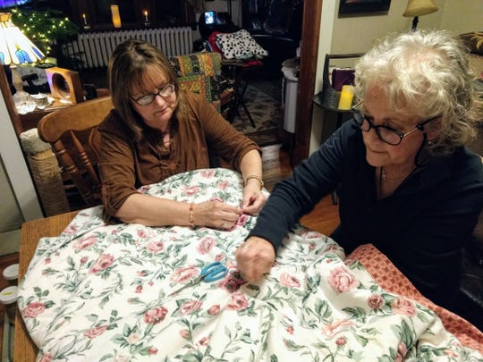 Lorna Koberlein, left, and Jill Marie Madigan sew a sleeping bag inside Madigan's Binghamton home. The two women sew sleeping bags for the homeless, as well as blankets and pet beds.
