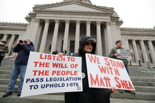 """Ed Yasukawa, of Seattle, holds a sign that reads """"We Stand With Matt Shea,"""" as he attends a rally, Monday, Jan. 13, 2020, on the first day of the 2020 session of the Washington legislature at the Capitol in Olympia, Wash. The embattled Rep. Matt Shea, R-Spokane Valley, returned to the Capitol Monday amid calls for his resignation following in the wake of a December report that found he was involved in anti-government activities."""