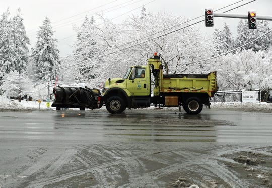 A snow plow drives through the intersection of Lincoln and Highway 305 in Poulsbo on Monday, Jan. 13, 2020.