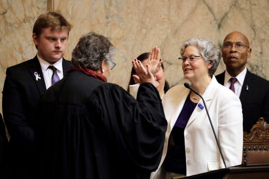 House Speaker Laurie Jinkins, D-Tacoma, second from right, is sworn in by former Washington Supreme Court Chief Justice Mary Fairhurst, second from left, Monday, Jan. 13, 2020, on the first day of the 2020 session of the Washington legislature at the Capitol in Olympia.