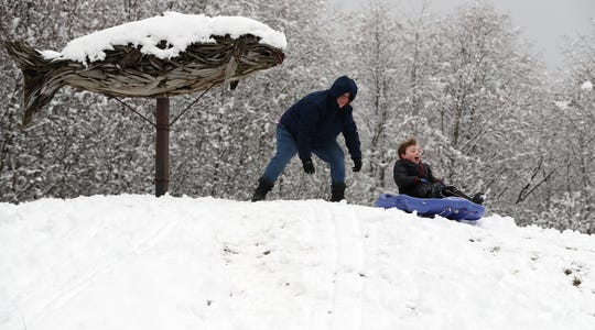 Dana Terry gives son Logan, 6, a push from the top of the hill while sledding at Fish Park in Poulsbo on Monday. The north end of Kitsap received the heaviest snow accumulation overnight Sunday and into Monday. Forecasters say another system could bring snow to the county mid-week.