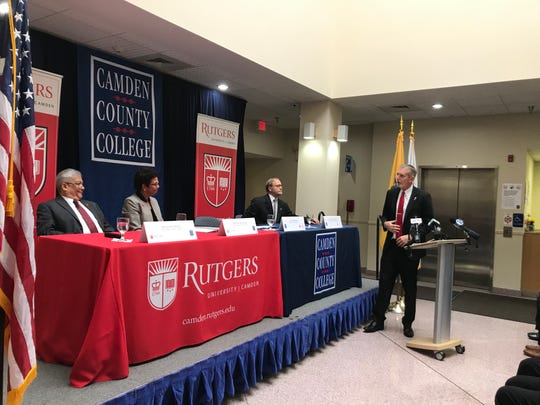 Camden County College President Don Borden shows off his red tie at as he joins Rutgers officials Michael Palis and Phoebe Haddon (center, seated) and David Edwards of CCC in announcing a new partnership between the two institutions.