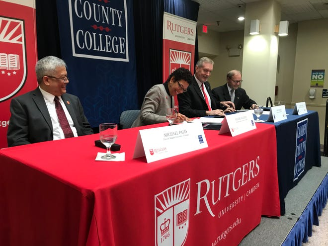 Rutgers-Camden Chancellor Phoebe Haddon signs a memorandum of understanding as Michael Palis (left to right), Don Borden and David Edwards watch.
