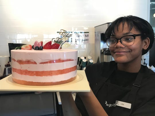 Eli Carthan shows off a strawberry cloud cake at Tous Les Jours, a new bakery in Cherry Hill.