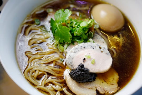An order of Black Truffle Shoyu is served at the Mochiko pop up inside of Money Chicken in downtown Cincinnati on Monday, Jan. 6, 2020. The bowl features truffle chashu, pork chashu, men, tamago and truffle pate for $18.