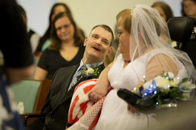 Bill Adams, who has cerebral palsy, and Sherri Daniel, who has a form of dwarfism, exchange vows at Christ Restoration Branch church in Lucasville on Jan. 4, after overcoming numerous obstacles to get married because of benefit penalties for people with disabilities.