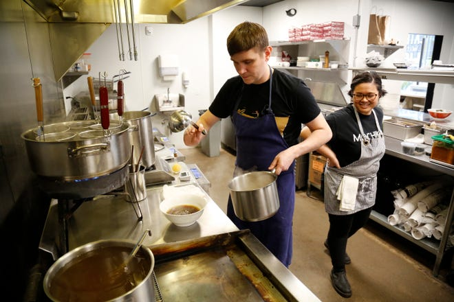 Partners Erik Bentz and Elaine Townsend prepare dishes ahead of a 6 p.m. opening at the Mochiko pop up inside of Money Chicken in downtown Cincinnati on Monday, Jan. 6, 2020.