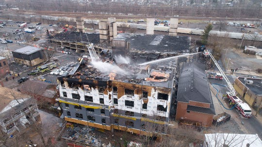 Firefighters continue to spray water Monday, January 13, 2020, on one of the buildings that were destroyed along Main Street in a multi-alarm fire the previous night.