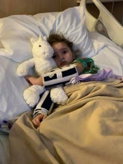 Jade DeLucia, a 4-year-old girl from Waterloo, finds comfort in a stuffed unicorn while she recovers from the flu.  Amanda Phillips / Special to the Register