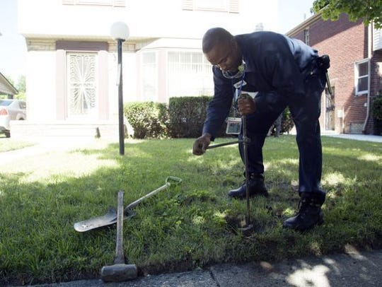 Homerich contractor Chester Clemons shuts off water on its Detroit Water and Sewerage Department bill on the 13000 block of Rutland Street in Detroit, Friday, July 15, 2014.