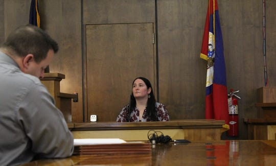 Wiper, right, on the witness stand at 21st District Court Monday.