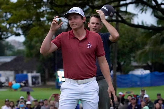 Cameron Smith celebrates his win on the 10th green after the final round of the Sony Open PGA Tour golf event, Sunday at Waialae Country Club in Honolulu. Smith defeated Brendan Steele, rear, in a one-hole playoff.